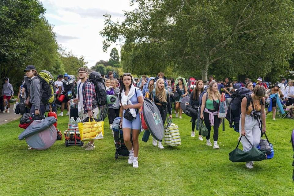 Festivalgoers walk along the towpath of the River Thames as they arrive for the Reading Festival (Steve Parsons/PA) (PA Wire)