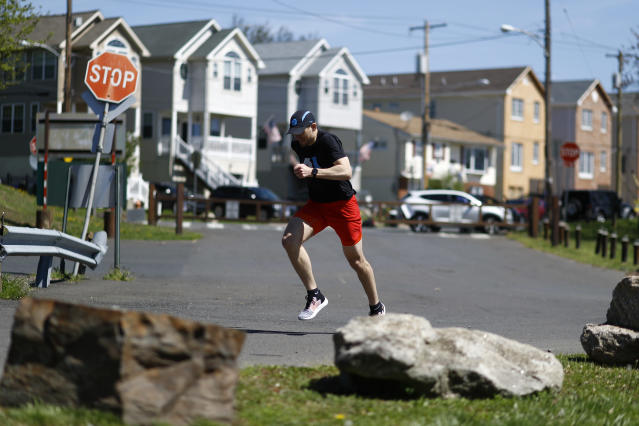 Fighter Kyle Daukaus sprints through Pleasant Hill Park while training near his home, Saturday, May 2, 2020, in Philadelphia. Daukaus, a rising star in the regional MMA promotion Cage Fury Fighting Championships, is still chasing his dream of getting the call to fight for UFC despite the coronavirus pandemic. (AP Photo/Matt Slocum)