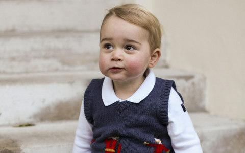An official photo of Prince George of Cambridge sitting in a courtyard at Kensington Palace, wearing a Cath Kidston jumper - Credit: - Source: AFP