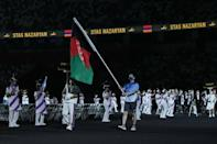 A Tokyo 2020 volunteer symbolically carried the Afghan flag during the Games opening ceremony (AFP/YASUYOSHI CHIBA)