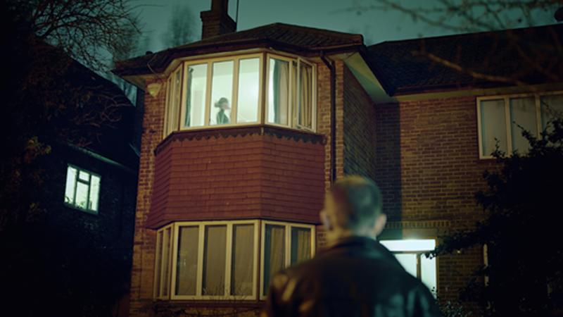 A file image of a man watching a woman through a window at night.