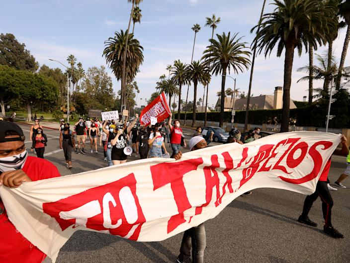 """Protesters carry a large banner with """"Tax Bezos"""" written in red."""