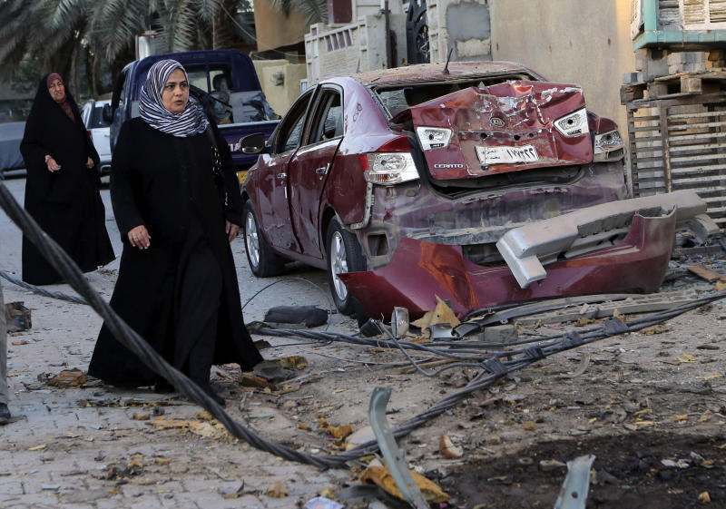 FILE - In this Oct. 8, 2013 file photo, women walk past the aftermath of a car bomb attack in the mainly Shiite neighborhood of Zafaraniyah in southeastern Baghdad, Iraq. Al-Qaida has come roaring back in Iraq since U.S. troops left in late 2011 and now looks stronger than it has in years. The terror group is capable of carrying out mass-casualty attacks several times a month, driving the death toll in Iraq to the highest level in half a decade. It sees each attack as a way to maintain an atmosphere of chaos that weakens the Shiite-led government's authority. (AP Photo/Hadi Mizban, File)