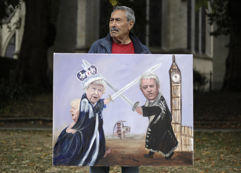 Political artist Kaya Mar holds his painting of British Prime Minister Boris Johnson, left, Britain's Queen Elizabeth II, center, and Speaker of the House of Commons John Bercow as he stands opposite Parliament Square in London, Tuesday, Sept. 3, 2019. Opposition parties are challenging British Prime Minister Boris Johnson's insistence that the U.K. will leave the EU on Oct. 31, 2019 even without a deal, setting up a pivotal day in British politics. (AP Photo/Matt Dunham)