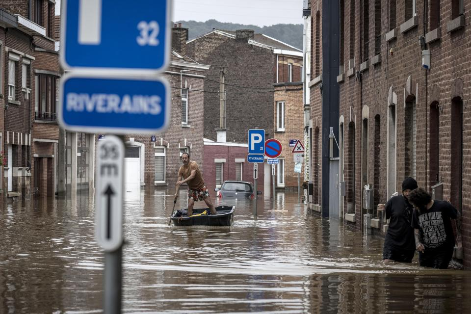 FILE-In this July 16, 2021 file photo a man rows a boat down a residential street after flooding in Angleur, Province of Liege, Belgium. Scientists say global warming makes the kind of extreme rainfall that caused deadly flash floods in western Europe last month more likely, though it remains unclear exactly how much.(AP Photo/Valentin Bianchi)
