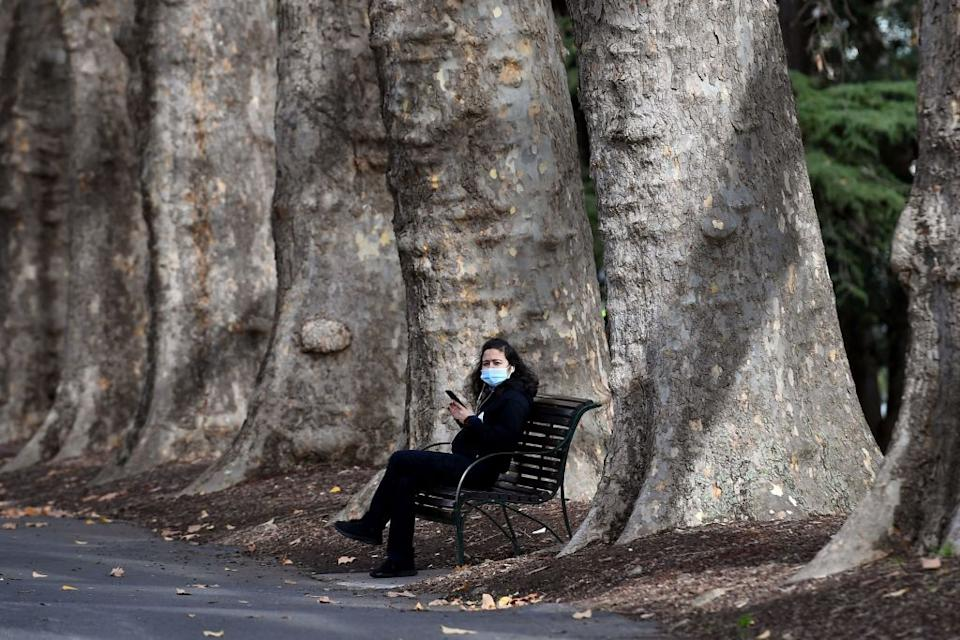A woman takes a break on a park bench in Melbourne as the coronavirus lockdown of Australia's second-biggest city was extended by another seven days, authorities announced on June 2.