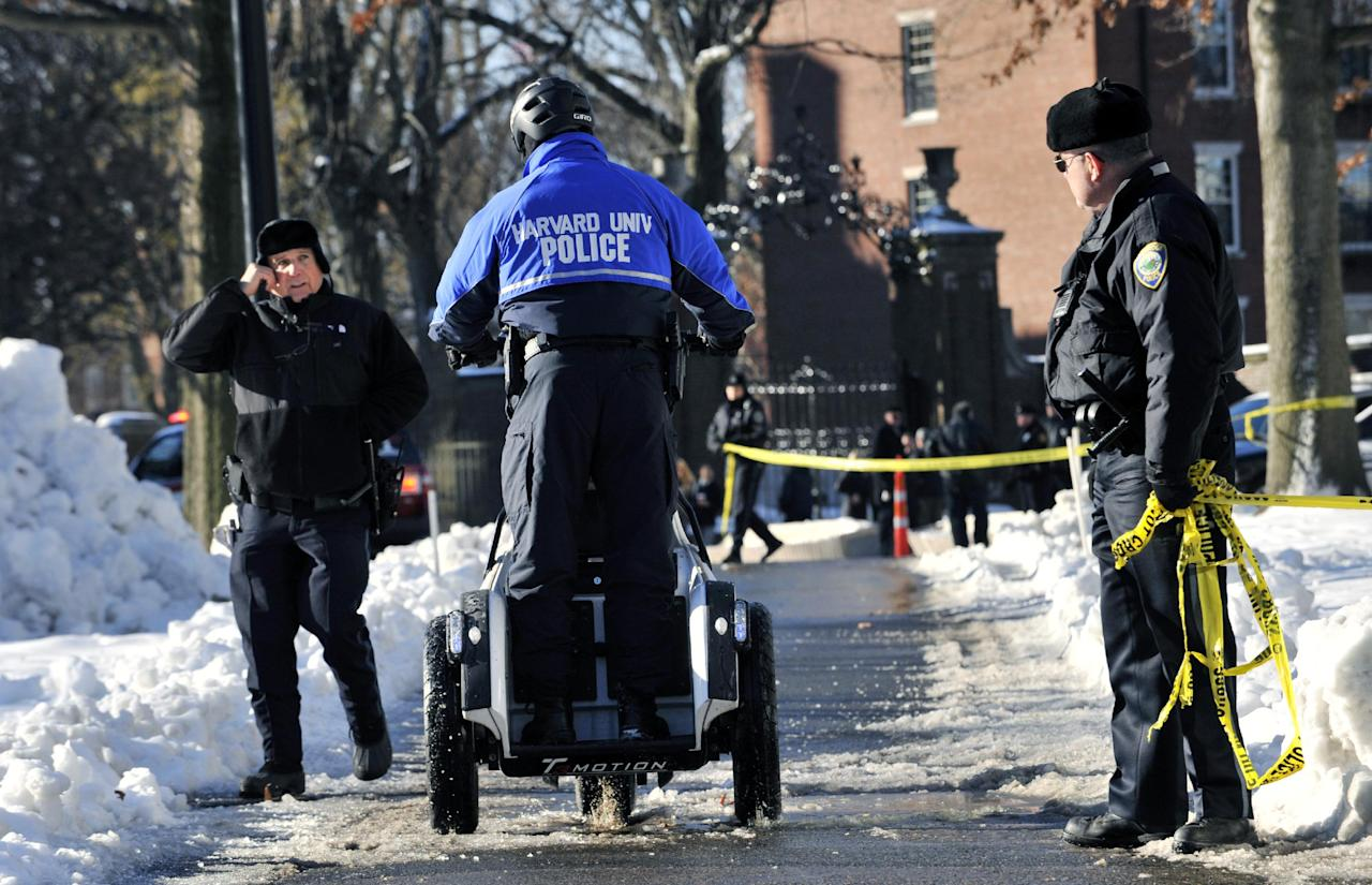 Police officers secure an area at Harvard University in Cambridge, Mass., Monday, Dec. 16, 2013. Four buildings on campus were evacuated after campus police received an unconfirmed report that explosives may have been placed inside, interrupting final exams. (AP Photo/Josh Reynolds)