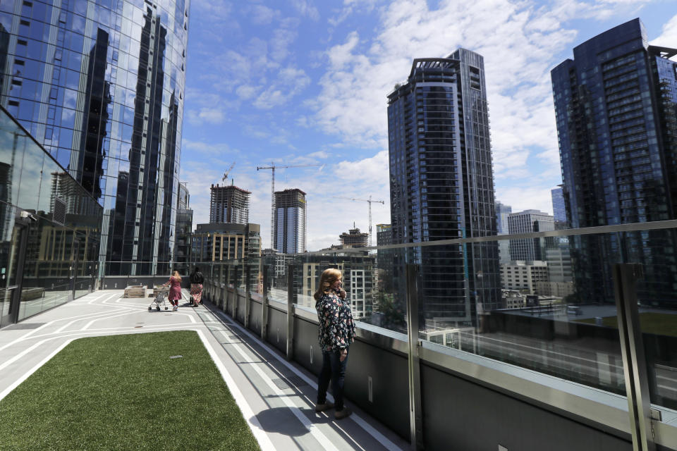 Connie Wade, center, looks out over the growing skyline of downtown Seattle, Wednesday, June 17, 2020, as she stands in an outdoor deck area at Mary's Place, a family homeless shelter located inside an Amazon corporate building on the tech giant's Seattle campus. The facility is home to the Popsicle Place shelter program, an initiative to address the needs of homeless children with life-threatening health conditions. (AP Photo/Ted S. Warren)