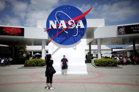 FILE PHOTO: Tourists take pictures of a NASA sign at the Kennedy Space Center visitors complex in Cape Canaveral, Florida