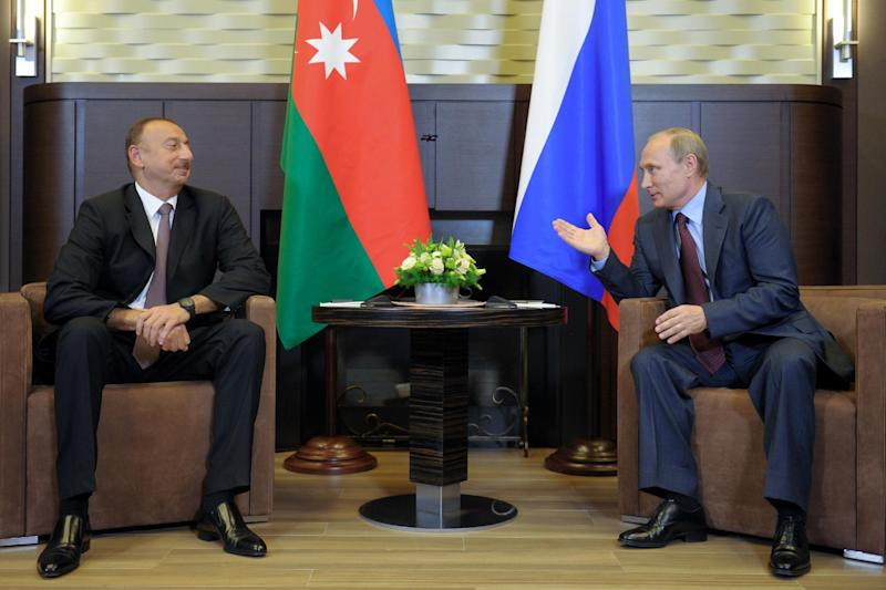 Russian President Vladimir Putin (right) speaks with his Azerbaijan counterpart Ilham Aliyev during their meeting at the Bocharov Ruchei residence outside Sochi on August 9, 2014