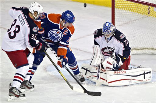 Columbus Blue Jackets' Sergei Bobrovsky (72) makes the save as Edmonton Oilers' Shawn Horcoff (10) and Adrian Aucoin(33) battle for the rebound during the second period of their NHL hockey game, Thursday, March 28, 2013, in Edmonton, Alberta. (AP Photo/The Canadian Press, Jason Franson)