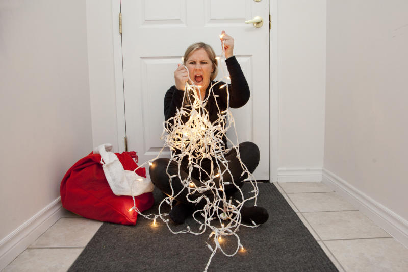 A frustrated woman can't get the christmas lights to untangle so she screams in anger