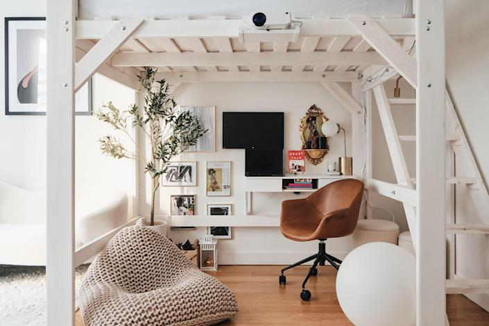 Above the study area, Candace's bed is lofted with white scaffolding. Black body candles from Beyond Interior complement framed Vogue spreads. The knit beanbag chair, floating desk, and artificial olive tree are from Etsy.