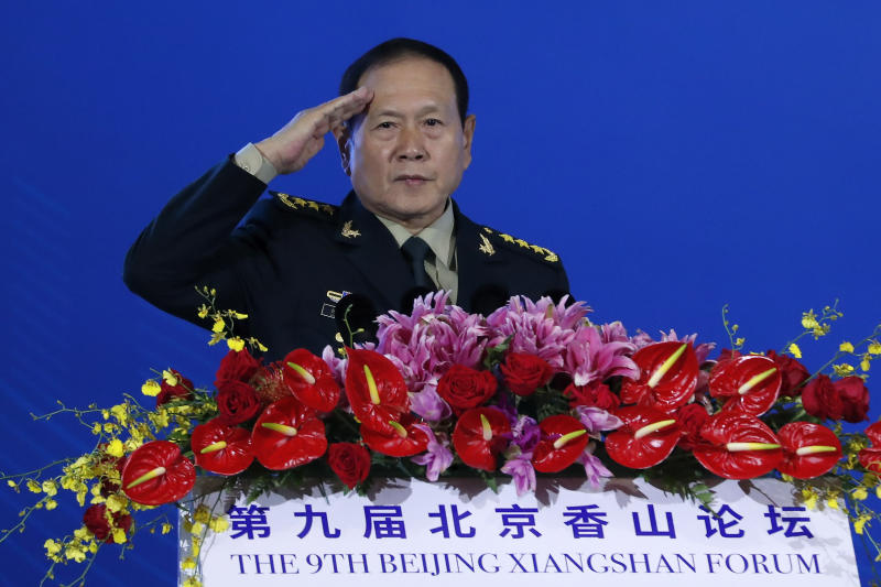 """Chinese Defense Minister Wei Fenghe salutes after delivering his opening speech for the Xiangshan Forum, a gathering of the region's security officials, in Beijing, Monday, Oct. 21, 2019. Wei issued a stinging rebuke of the U.S. at a defense forum in Beijing, saying China wasn't fazed by sanctions, pressure and a """"big stick policy."""" (AP Photo/Andy Wong)"""