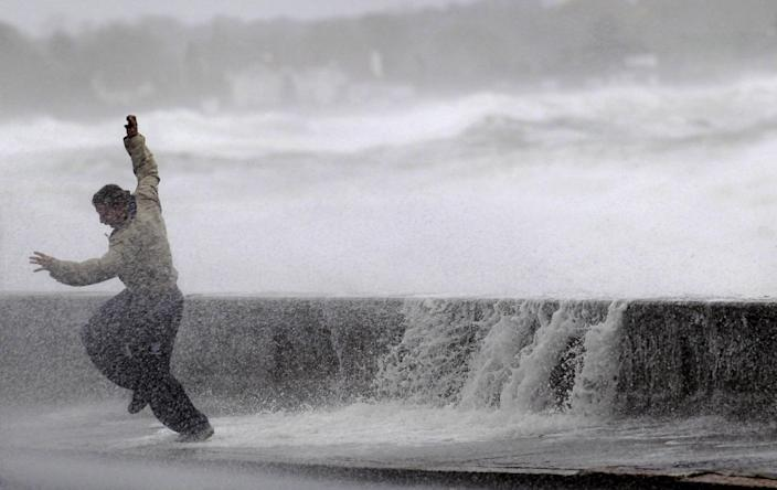 A man reacts to waves crashing over a seawall in Narragansett, R.I., Monday, Oct. 29, 2012. A fast-strengthening Hurricane Sandy churned north Monday, raking ghost-town cities along the Northeast corridor with rain and wind gusts. (AP Photo/Steven Senne)
