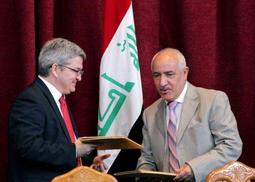 Premier Oil executive Stuart Morrison (left) exchanges documents with Dhia Jaafar -- the head of Iraq's state-owned South Oil Company. Iraq has signed a deal with Russia's Bashneft and Britain's Premier Oil to explore an area believed to hold oil, the latest step in Baghdad's efforts to boost its role as a global energy supplier