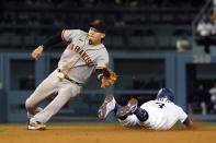 Los Angeles Dodgers' Chris Taylor, right, steals second base past San Francisco Giants third baseman Wilmer Flores during the fifth inning of a baseball game Wednesday, July 21, 2021, in Los Angeles. (AP Photo/Marcio Jose Sanchez)