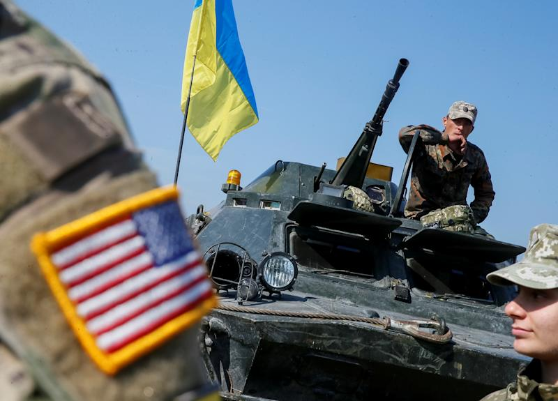 "A military instructor of the U.S. Army is seen near Ukrainian servicemen during multinational drills ""Rapid Trident 2019"" at the International Peacekeeping and Security Center near Lviv, Ukraine Sept. 24, 2019. (Photo: Gleb Garanich/Reuters)"