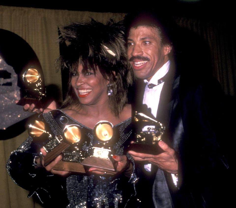 <p>Tina Turner backstage at the Grammys with Lionel Richie, showing off her multiple awards. </p>