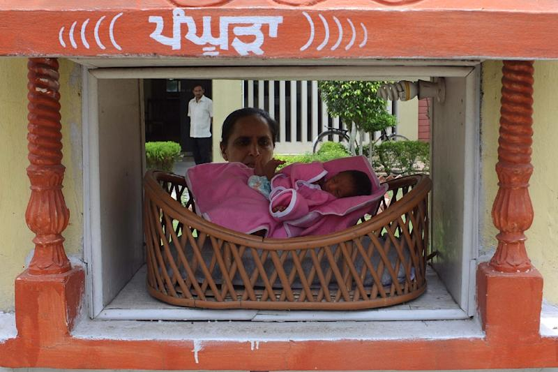 File picture shows an Indian Red Cross Society employee with an abandoned baby boy in a 'pangpura' (cradle) drop off box at the entrance to the Red Cross House in Amritsar (AFP Photo/Narinder Nanu)