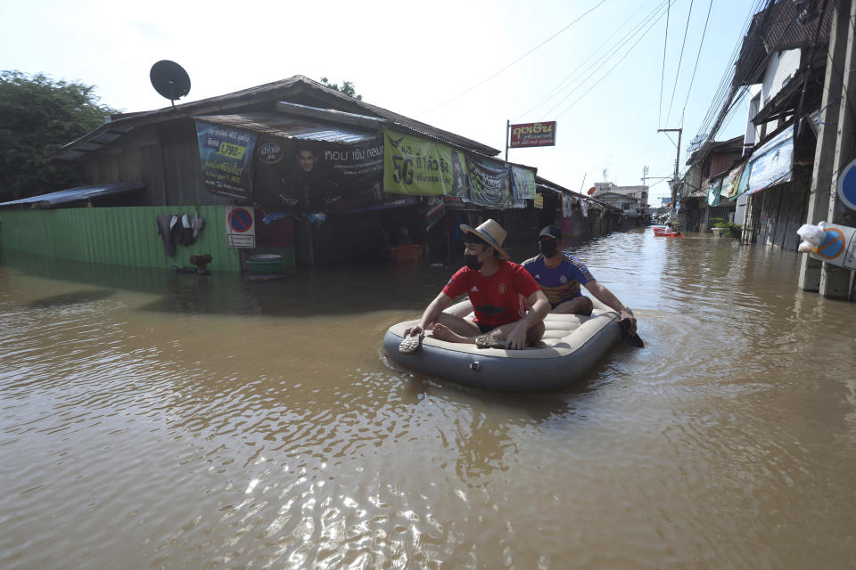 A Thai resident rows his float for his friend on a flooded street in Ayutthaya province, north of Bangkok, Thailand, Tuesday, Oct. 5, 2021. As flood waters continued to inundate areas in northern and central Thailand and were starting to hit low-lying areas in the capital, Thai officials were looking warily ahead Tuesday the possibility of more storms this month, but were optimistic the devastation of a decade ago would not be repeated. (AP Photo/Nathathida Adireksarn)