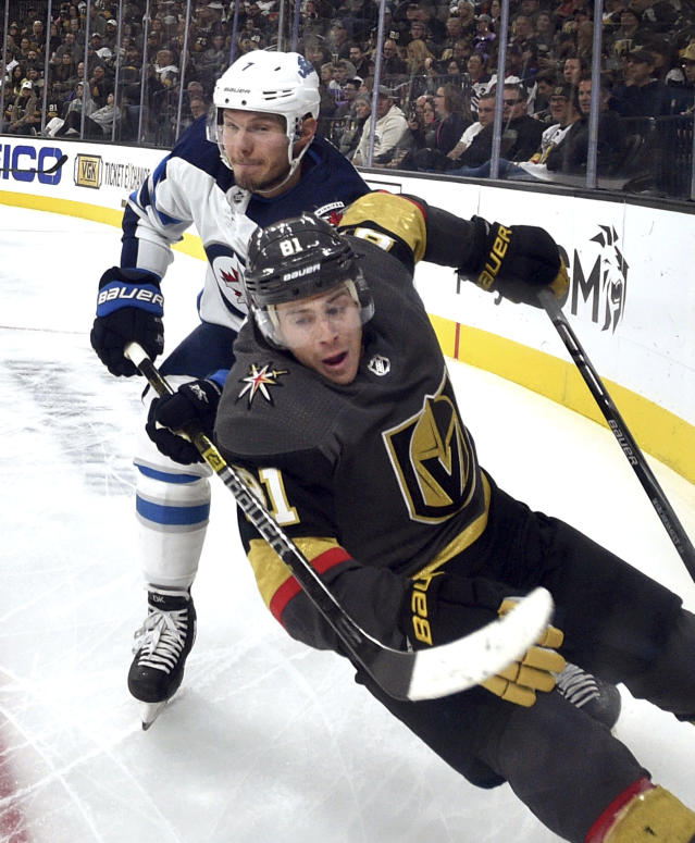 Vegas Golden Knights center Jonathan Marchessault (81) is tripped up by Winnipeg Jets defenseman Dmitry Kulikov during the second period of an NHL hockey game Saturday, Nov. 2, 2019, in Las Vegas. (AP Photo/David Becker)