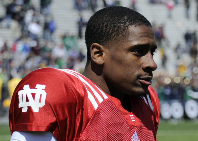 """FILE - In this April 20, 2013, file photo, Notre Dame quarterback Everett Golson walks off the fieldduring the Blue-Gold spring scrimmage NCAA college football in South Bend, Ind. Golson says he was suspended from the university for the fall semester for using """"poor judgment on a test."""" He had previously said he was suspended for using poor academic judgment, but in an interview with Sports Illustrated he specified that it came during a test.(AP Photo/Joe Raymond, File)"""