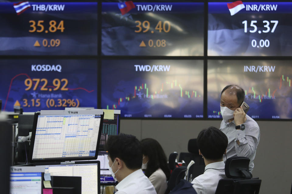 A currency trader wearing a face mask talks with his colleague at the foreign exchange dealing room of the KEB Hana Bank headquarters in Seoul, South Korea, Tuesday, April 6, 2021. Asian shares were mixed Tuesday after a Wall Street rally that reflected some optimism about the economy recovering from the damage of the coronavirus pandemic. (AP Photo/Ahn Young-joon)