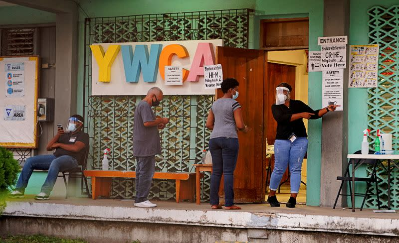People queue to enter a polling station to cast their votes during the election for a new prime minister, in Belize City