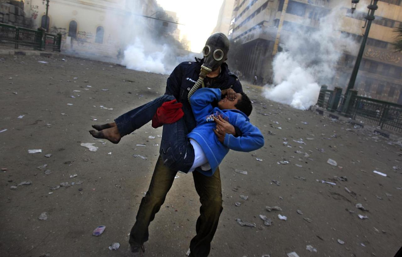 An Egyptian protester evacuates an injured boy during clashes near Tahrir Square, Cairo, Egypt, Friday, Jan. 25, 2013. Two years after Egypt's revolution began, the country's schism was on display Friday as the mainly liberal and secular opposition held rallies saying the goals of the pro-democracy uprising have not been met and denouncing Islamist President Mohammed Morsi. (AP Photo/Khalil Hamra)