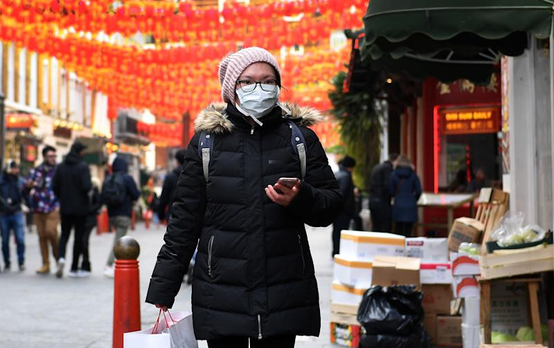A woman covers her face while visiting a Chinatown in London during the coronavirus outbreak. Source: AAP