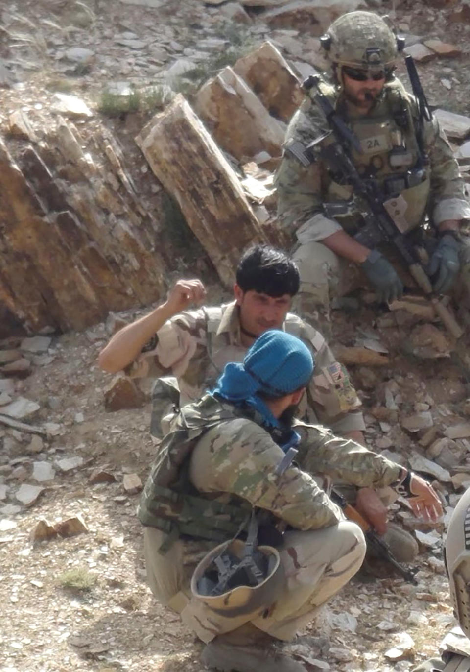 In this undated photo provided by Ryan Brummond, Mohammad Khalid Wardak, center, speaks to a U.S. solider in Afghanistan in Afghanistan. Khalid, as he's called by his friends, had no intention of leaving Afghanistan, where he was a high-profile national police officer who'd worked alongside American special forces to defeat the Taliban. Then with stunning speed, his government collapsed. Now he is in hiding with his wife and four children, wounded and hunted by the Taliban, desperately hoping that American officials will repay his loyalty by helping his family escape almost certain death. (Ryan Brummond via AP)