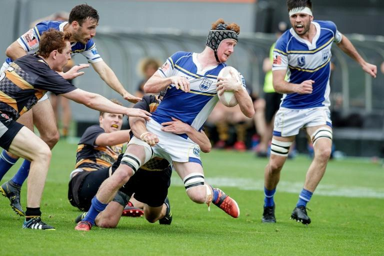 University Squids' George Hitchcock (C) is tackled in the U85kg national final against Eden Lizards in Auckland
