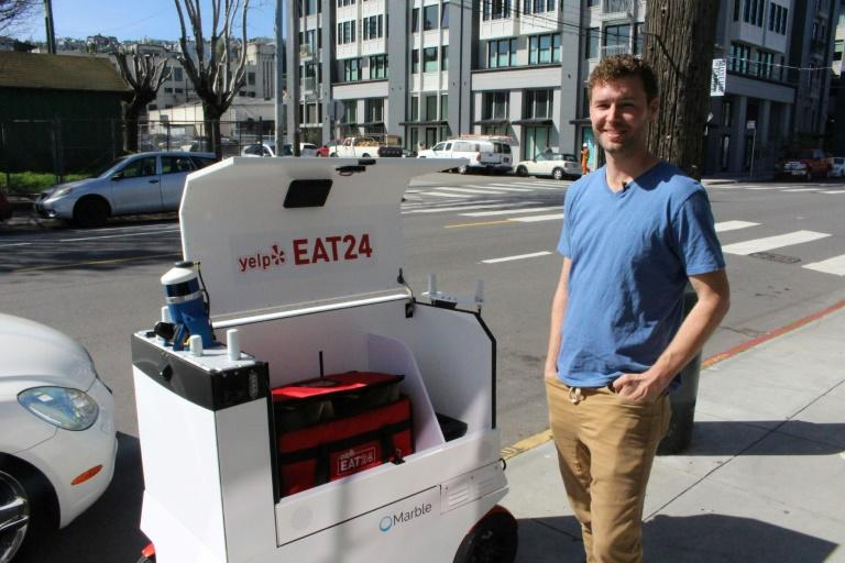 "Marble co-founder Matthew Delaney prepares a ""Happy"" ground-delivery robot outside the startup's headquarters in San Francisco, on March 29, 2017"