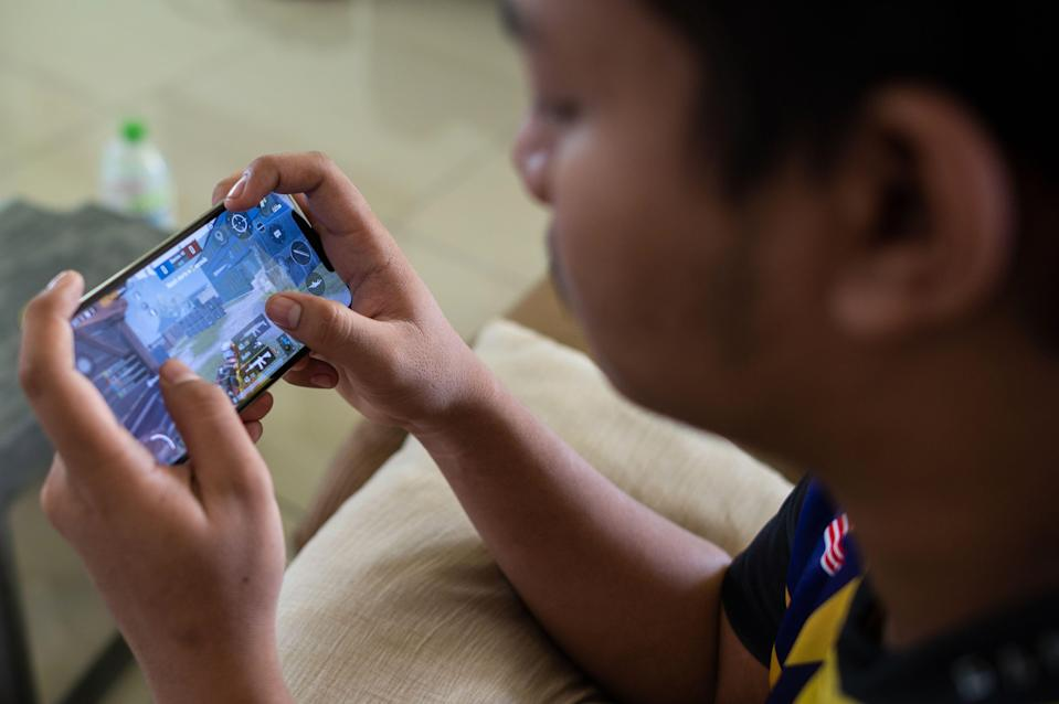 This picture taken on August 22, 2020 shows stateless eSports player Muhammad Aiman Hafizi Ahmad, 20, playing PlayerUnknown's Battlegrounds (PUBG), an online multiplayer gaming on his mobile phone at a house used by his gaming team in Bangi town, south of Kuala Lumpur. - Muhammad Aiman Hafizi, a rising eSports star was granted Malaysian citizenship on September 1, after a lengthy battle, in a victory that will pave the way for him to compete internationally. (Photo by Mohd RASFAN / AFP) / To go with 'MALAYSIA-RIGHTS-ESPORTS,FOCUS' by Patrick LEE / The erroneous mention[s] appearing in the metadata of this photo by Mohd RASFAN has been modified in AFP systems in the following manner: [at a house used by his gaming team] instead of [his family's house]. Please immediately remove the erroneous mention[s] from all your online services and delete it (them) from your servers. If you have been authorized by AFP to distribute it (them) to third parties, please ensure that the same actions are carried out by them. Failure to promptly comply with these instructions will entail liability on your part for any continued or post notification usage. Therefore we thank you very much for all your attention and prompt action. We are sorry for the inconvenience this notification may cause and remain at your disposal for any further information you may require. (Photo by MOHD RASFAN/AFP via Getty Images)