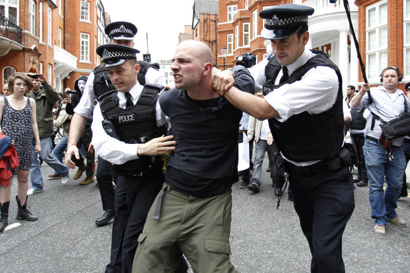 British police officers arrest a protesters in support of WikiLeaks founder Julian Assange from the front of Ecuadorian Embassy in central London, London, Thursday, Aug. 16, 2012. WikiLeaks founder Julian Assange entered the embassy in June in an attempt to gain political asylum to prevent him from being extradited to Sweden, where he faces allegations of sex crimes, which he denies. (AP Photo/Sang Tan)