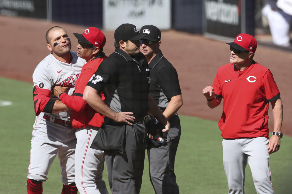 Cincinnati Reds' Joey Votto, left, is held back by bench coach Freddie Benavides as manager David Bell, right, argues with umpire Ryan Additon (67) in the first inning of a baseball game against the San Diego Padres, Saturday, June 19, 2021, in San Diego. (AP Photo/Derrick Tuskan)