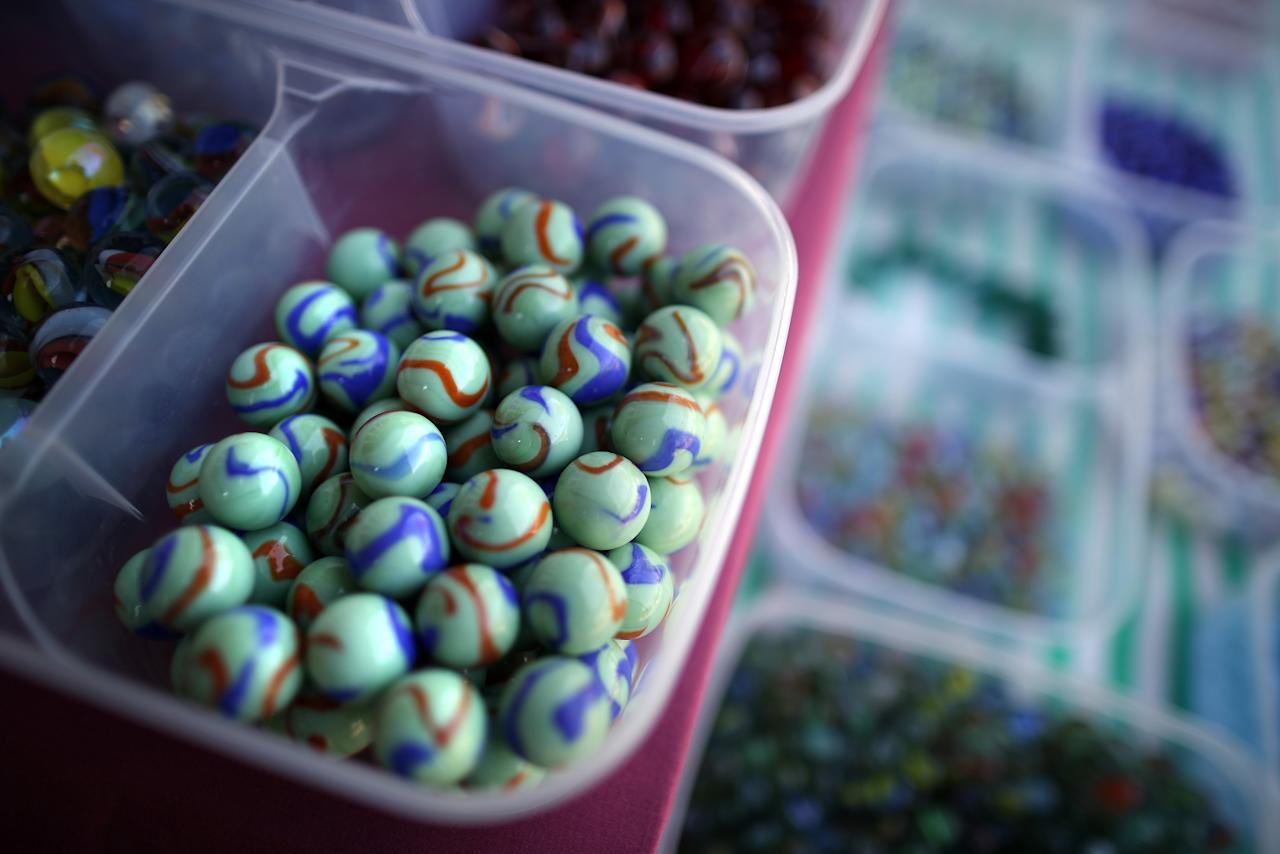 Marbles are displayed for sale at the British and World Marble Championships  on April 6, 2012 in Tinsley Green, England.  On Good Friday every year, contestants from all over the world gather at The Greyhound pub in Tinsley Green, Sussex to take part in the Championships. The game is played between two teams of six players in a ring with a diameter of six feet. The object of the game is to knock 25 out of 49 'target marbles' out of the ring using 'tolley' marbles before the opposing team. (Photo by Peter Macdiarmid/Getty Images)