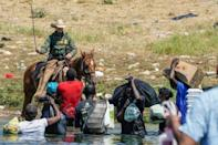 A United States Border Patrol agent on horseback uses his reins as he tries to stop Haitian migrants from entering an encampment on the banks of the Rio Grande river near the International Bridge in Del Rio, Texas (AFP/PAUL RATJE)
