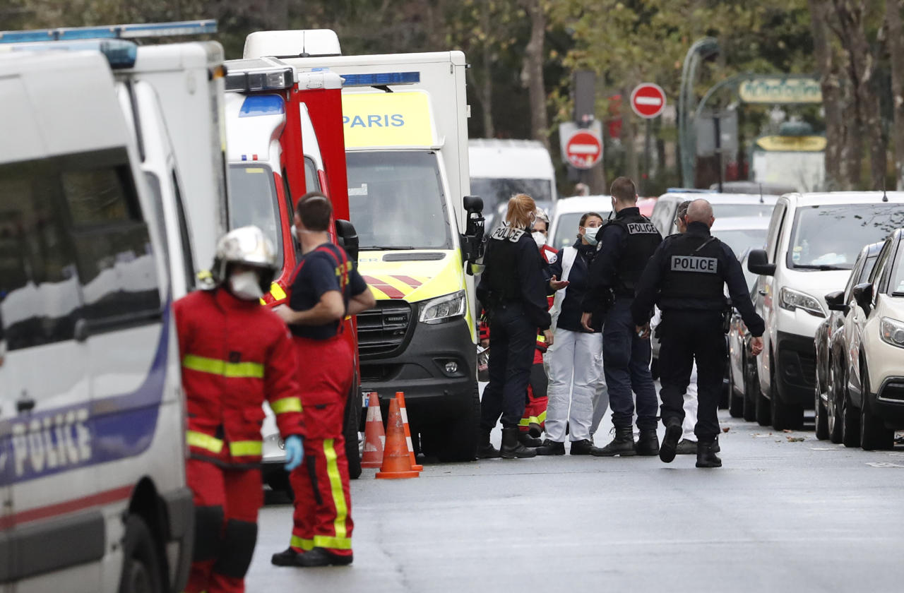 "French police officers and rescue workers gather a knife attack near the former offices of satirical newspaper Charlie Hebdo, Friday Sept. 25, 2020 in Paris. A police official said officers are ""actively hunting"" for the perpetrators and have cordoned off the area including the former Charlie Hebdo offices after a suspect package was noticed nearby. Islamic extremists attacked the offices in 2015, killing 12 people. (AP Photo/Thibault Camus)"