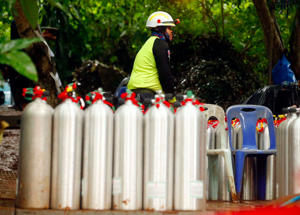 A Thai rescuer prepares oxygen tanks for diving (Picture: PA)