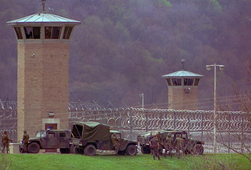 FILE - This April 28, 1993 file photo shows law officers and National Guard troops assembling outside the Southern Ohio Correctional Facility as a riot by inmates enters its 10th day in Lucasville, Ohio. In the 20 years since the nation's longest deadly prison riot broke out in Lucasville, no interviews have been granted with the five men sentenced to death in the killing of a guard. Yet time has brought new evidence and insights that will dominate events marking the 20th anniversary of the 11-day siege of April 1993. (AP Photo/Mark Duncan, File)
