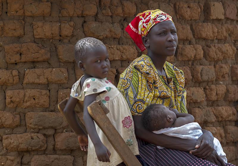 Rose Akurut, a mother of five, sits outside her father's home in Uganda's Bukedea district on September 25, 2014, after she was chased away by her husband who is now demanding a refund of the dowry he paid for Rose (AFP Photo/Isaac Kasamani)