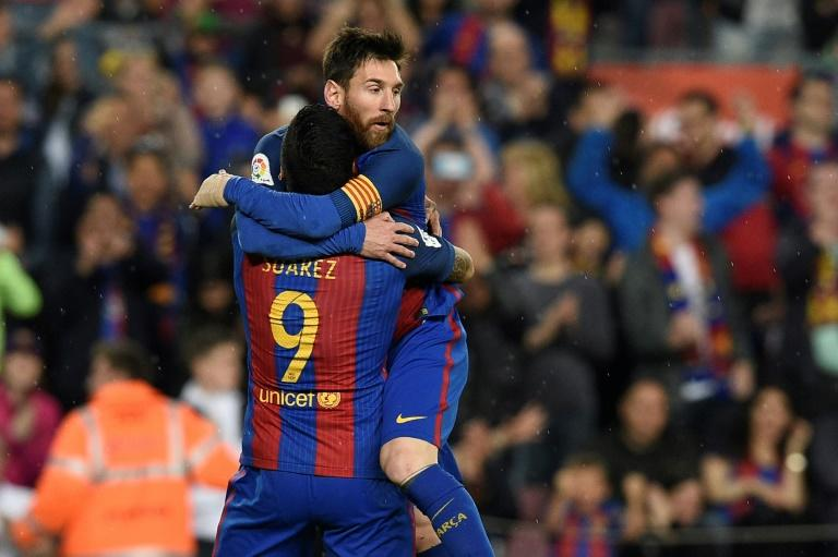 Barcelona's forward Lionel Messi (R) celebrates with Barcelona's  forward Luis Suarez after scoring a goal during the Spanish league football match FC Barcelona vs Real Sociedad at the Camp Nou stadium in Barcelona on April 15, 2017