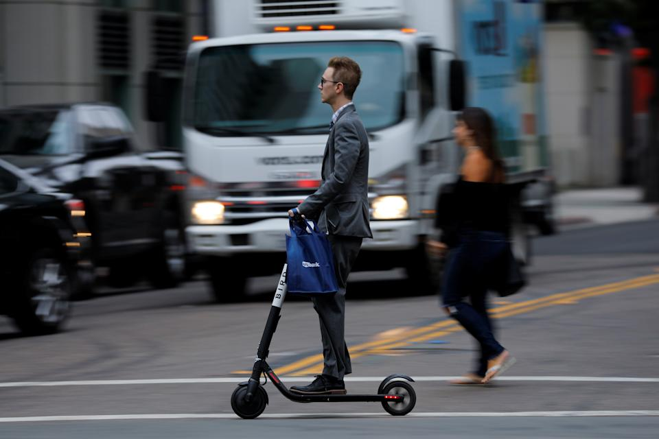 A man in a suit rides an electric BIRD rental scooter along a city street in San Diego, California, U.S. September 4, 2018.REUTERS/Mike Blake