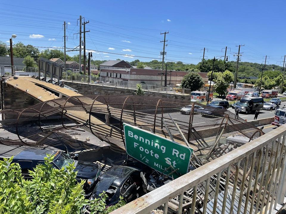 Two vehicles lay underneath a pedestrian bridge that collapsed on an interstate in northeast Washington D.C. Wednesday. The cause of the collapse is under investigation.