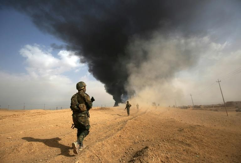 Iraqi forces and members of the Hashed al-Shaabi (Popular Mobilisation units) advance towards the city of Al-Qaim, near Syria during the fight against remnant pockets of Islamic State group jihadists on November 3, 2017