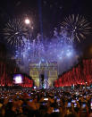 Revellers photograph fireworks over the Arc de Triomphe as they celebrate the New Year on the Champs Elysees, in Paris, France, Wednesday, Jan. 1, 2020. (AP Photo/Christophe Ena)