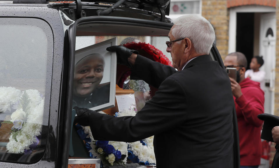 Staff of a funeral service place a picture of Jermaine Wright, a referee of the Hackney Marshes grassroots football league who died of COVID-19, into the hearse in front of his house in London, Thursday, June 11, 2020.(AP Photo/Frank Augstein)