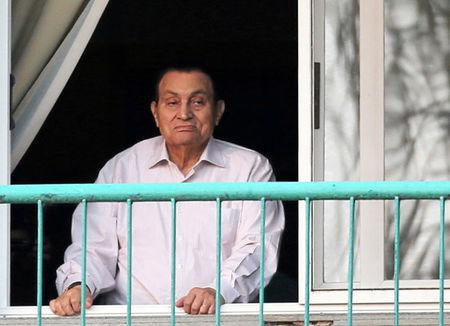 FILE PHOTO - Ousted Egyptian president Mubarak looks towards his supporters outside the area where he is hospitalized during the celebrations of the 43rd anniversary of the 1973 Arab-Israeli war, at Maadi military hospital